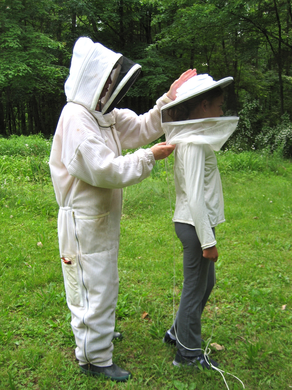 Laura in her beekeeper suit helping Sam to get her veil on.