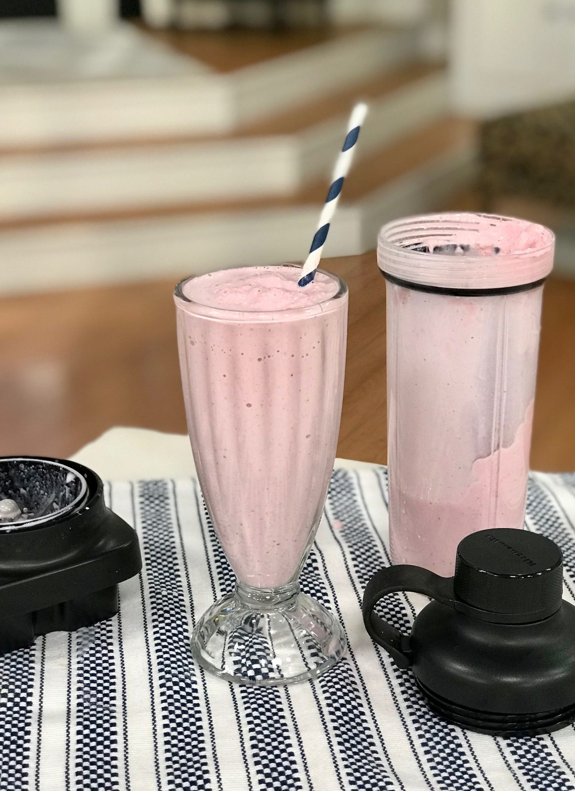 strawberry milkshake in glass with straw, KitchenAid personal blending jar off to the side
