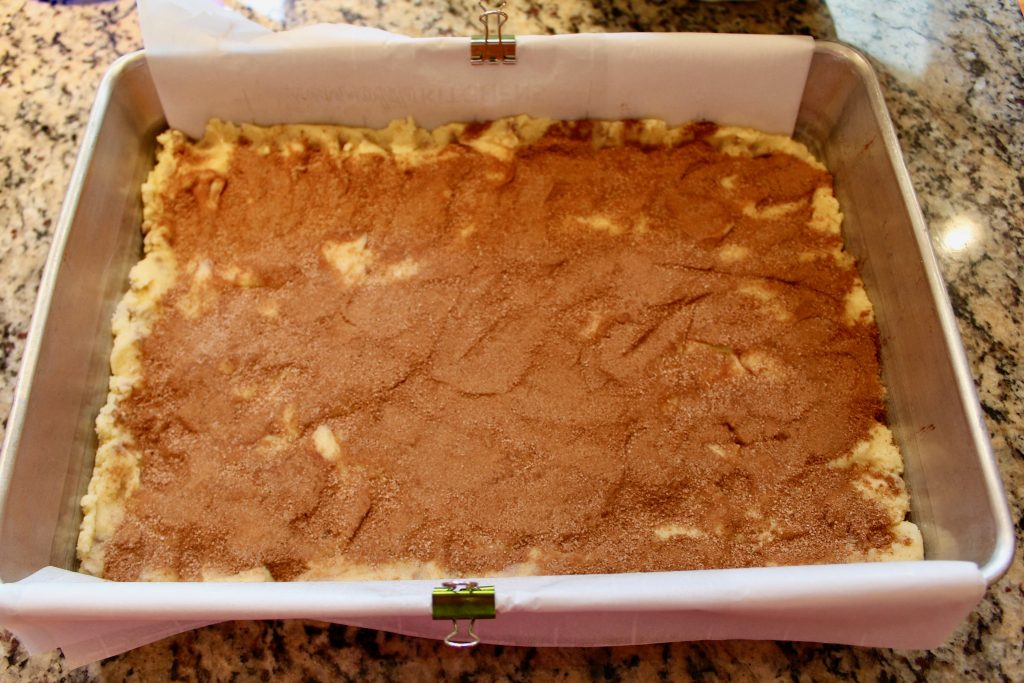 Cinnamon Chip Snickerdoodle Bars in 13x9x2-inch aluminum pan with parchment sling held in place with binder clips and sprinkled with cinnamon sugar
