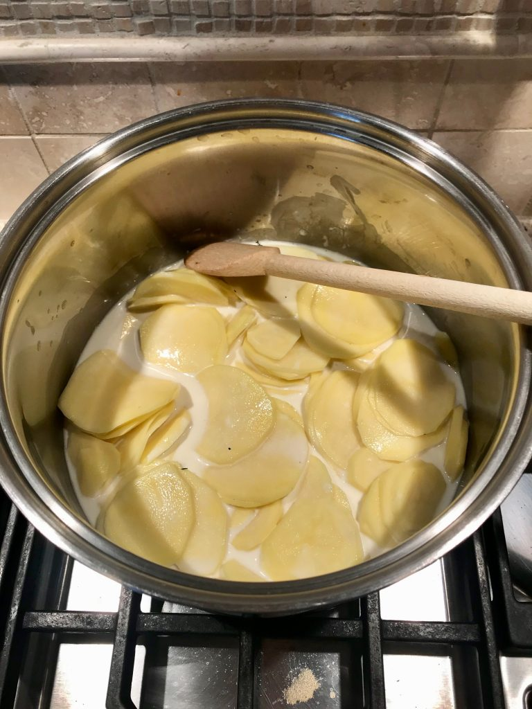 Step 1 of cooking potatoes for Creamy Potatoes Au Gratin - pot with sliced potatoes cooking in broth/cream mixture.