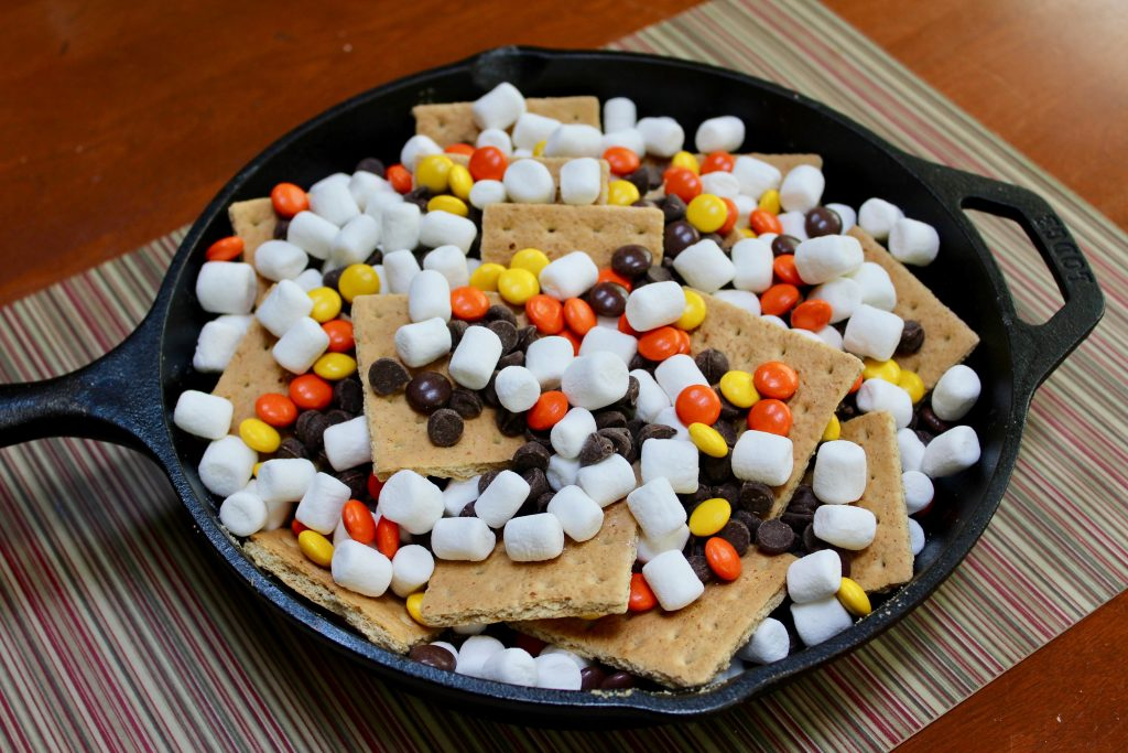 "Layer the graham crackers, chocolate chips, peanut butter candies and mini marshmallows in 10"" black cast iron Lodge skillet"