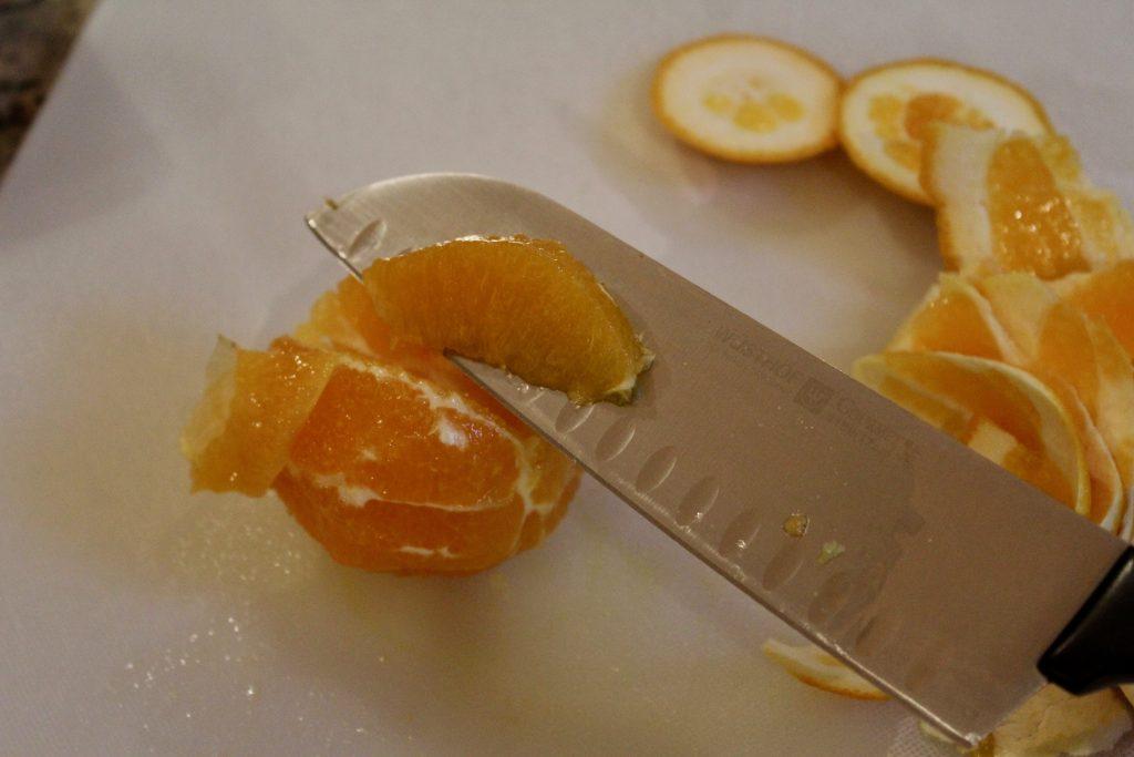 Cutting orange segments, using santoku knife to cut other side of orange membrane to release orange segment.