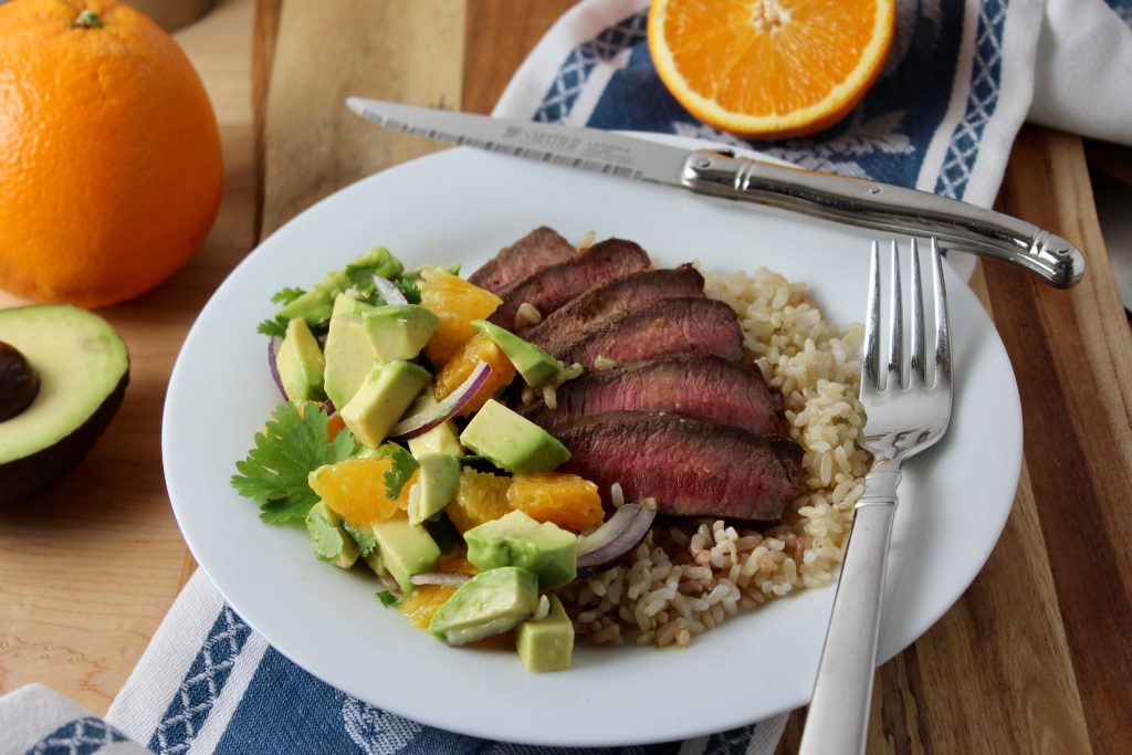 white round plate with brown rice, topped with fanned out grilled flat iron steak grilled medium with orange avocado salsa to the side.