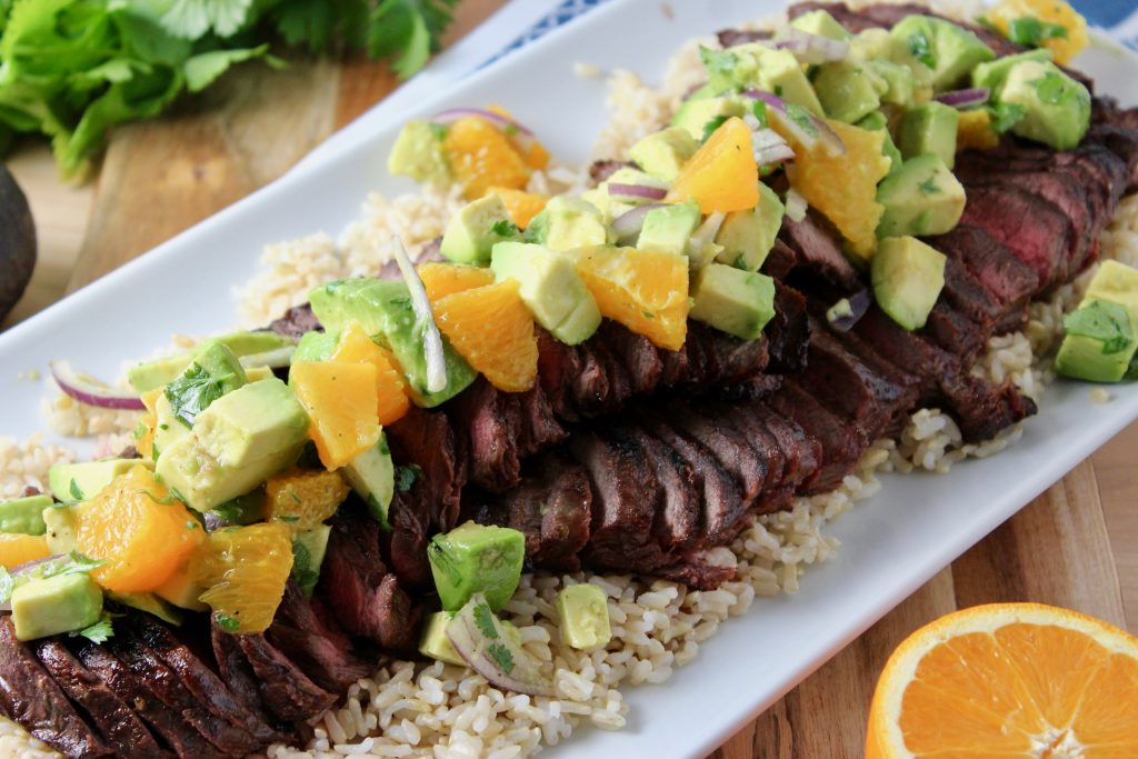 rectangular white platter with a bed of brown rice and thinly sliced grilled flat iron steak topped with orange avocado salsa.