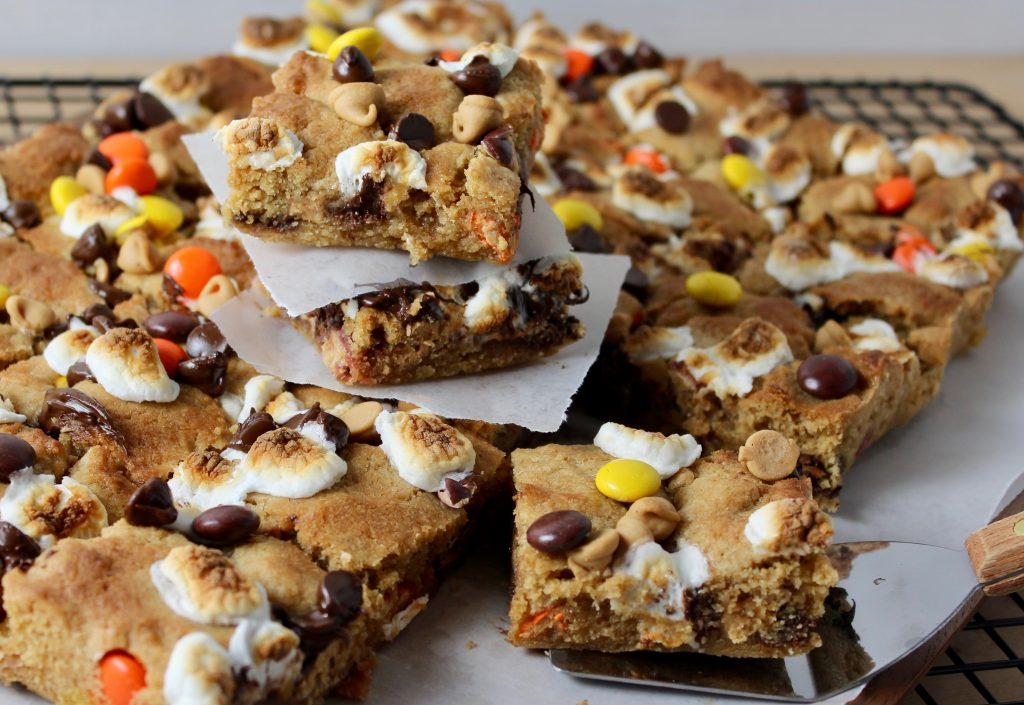 Peanut Butter S'mores Cookie Bars - close up photo of bars cut, 2 stacked between parchment squares and one on spatula