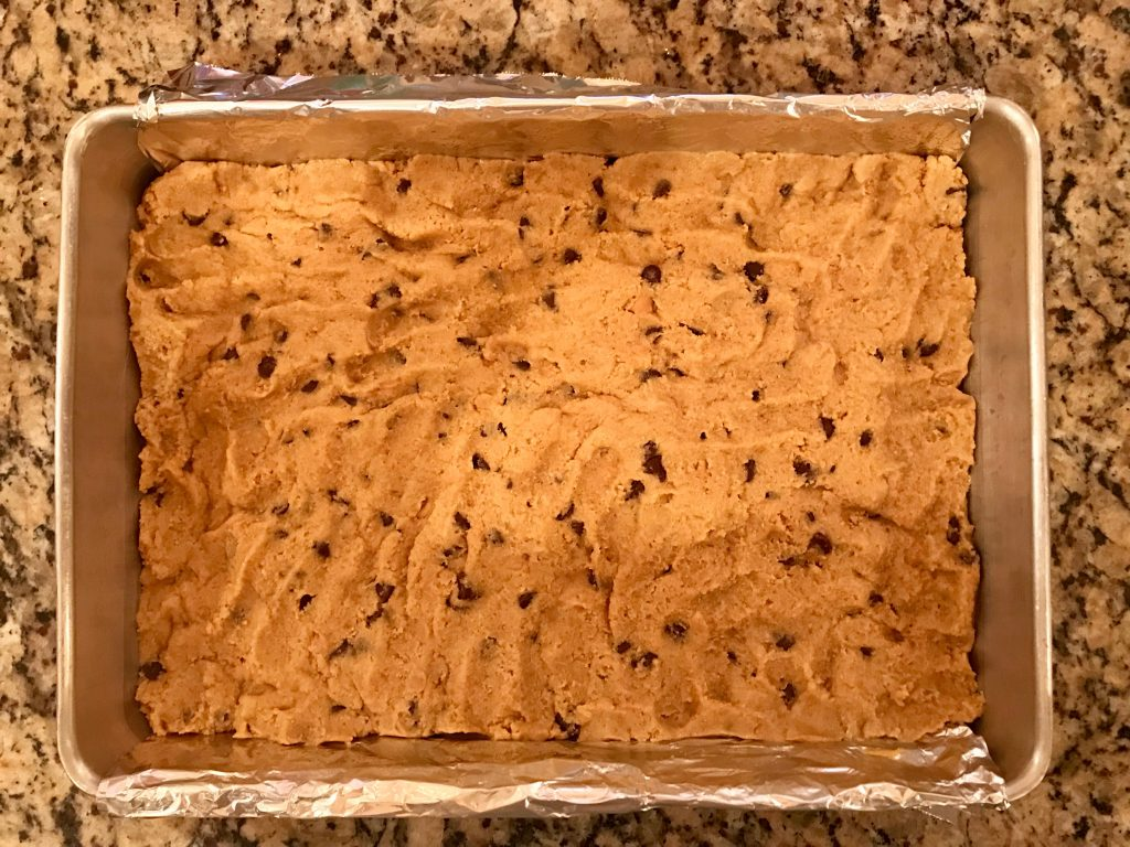 Peanut Butter S'mores Cookie Bars - 9x13x2-inch aluminum pan fitted with foil sling with dough spread in pan