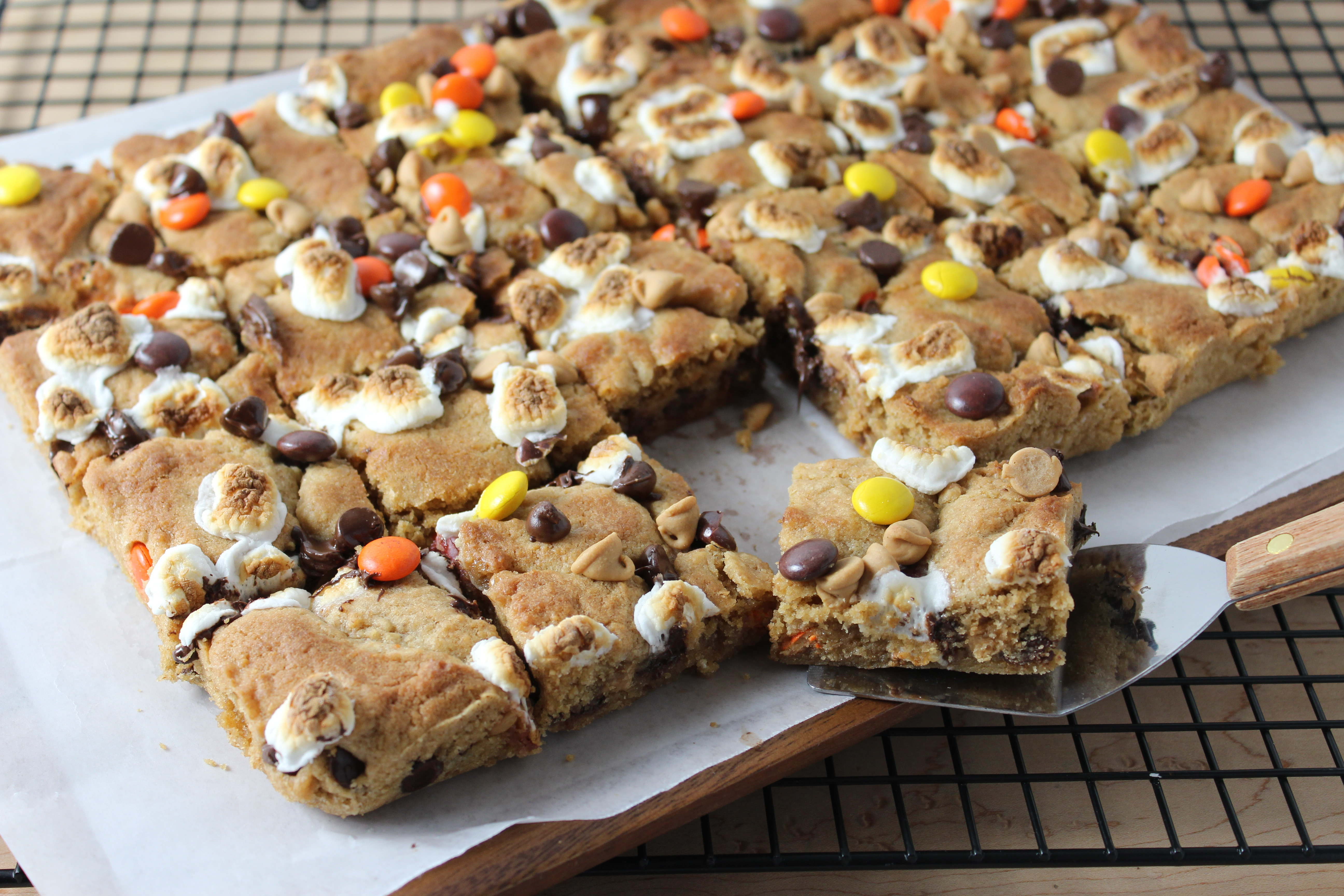 Peanut Butter S'mores Cookie Bars - close up photo of bars cut and one on spatula