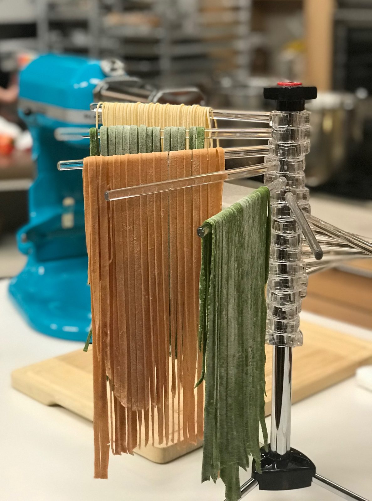 KitchenAid pasta drying rack with plain, tomato and spinach spaghetti and fettucini pasta hanging from rack. KitchenAid stand mixer with pasta roller attachment in background
