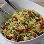 Broccoli Slaw with red peppers, snow peas, almonds and toasted ramen noodles in a white asymmetrical bowl