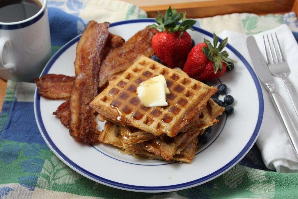 Yeasted Waffles: Photo showing blue rimmed white plate with stacked square waffles topped with butter and syrup. Strawberries and thick cut bacon on the plate as well. Coffee off to the side.