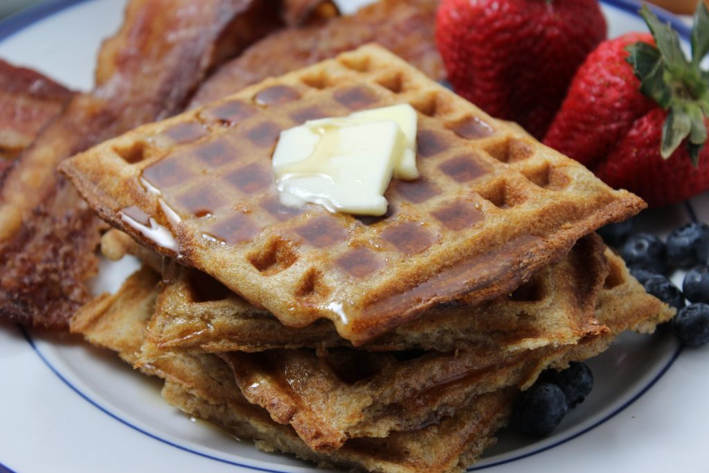 Yeasted Waffles: Close up photo of stacked square waffles with some pats of butter in the center and syrup dripping off the edges.