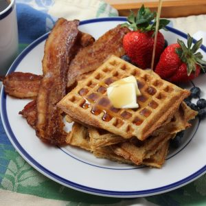 Yeasted Waffles: Syrup pouring onto stack of waffles on a plate with bacon and strawberries