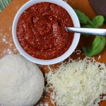 Bowl of easy homemade pizza sauce on pizza peel with shredded mozzarella, fresh pizza dough and sprig of fresh basil