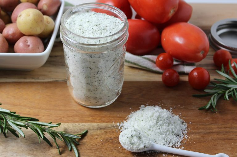 Homemade Rosemary Salt in mason jar on cutting board with vegetables and fresh rosemary