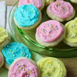 Cream Cheese Sugar cookies frosted in light pink, yellow and blue with nonpareil sprinkles - arranged on green glass platter