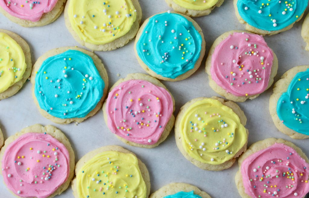 Cream Cheese Sugar cookies frosted in light pink, yellow and blue with nonpareil sprinkles - overhead shot of cookies on parchment