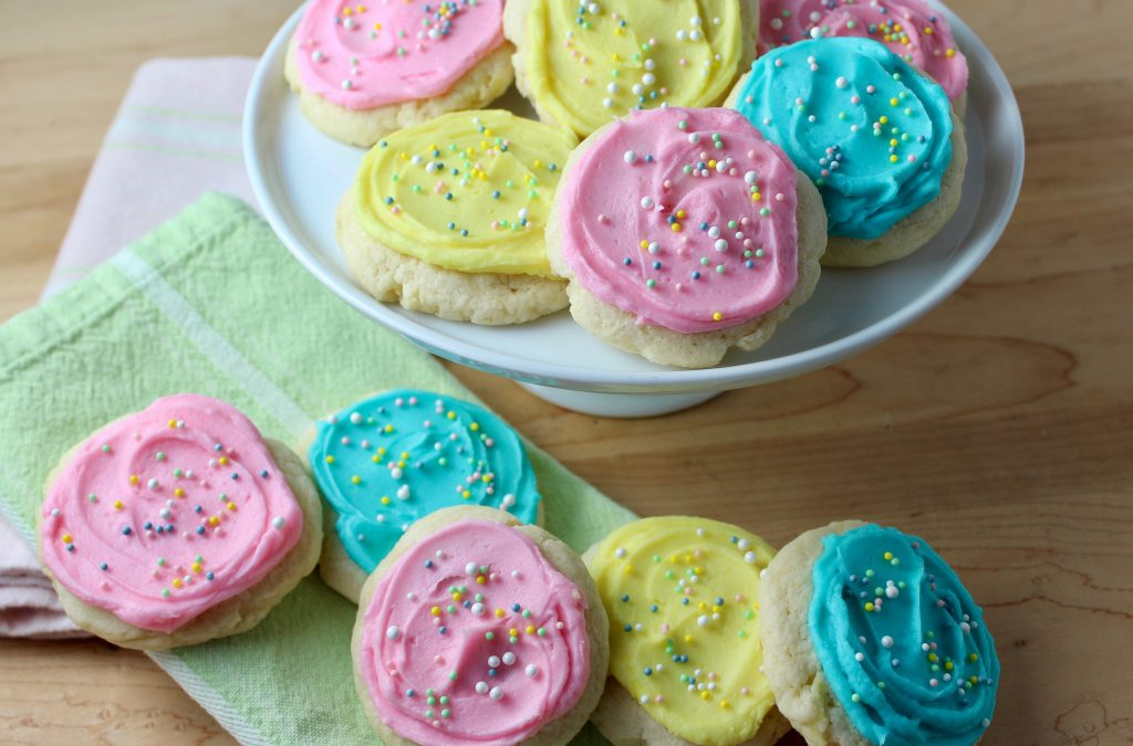 Cream Cheese Sugar cookies frosted in light pink, yellow and blue with nonpareil sprinkles - arranged on white pedestal