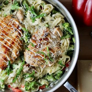 All-Clad Large Skillet filled with fettuccini in Parmesan cream sauce, with broccoli, red pepper and topped with sliced grilled chicken