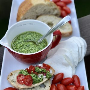 White rectangular tray with bread, spinach basil pesto in a red cup, mozzarella and grape tomatoes
