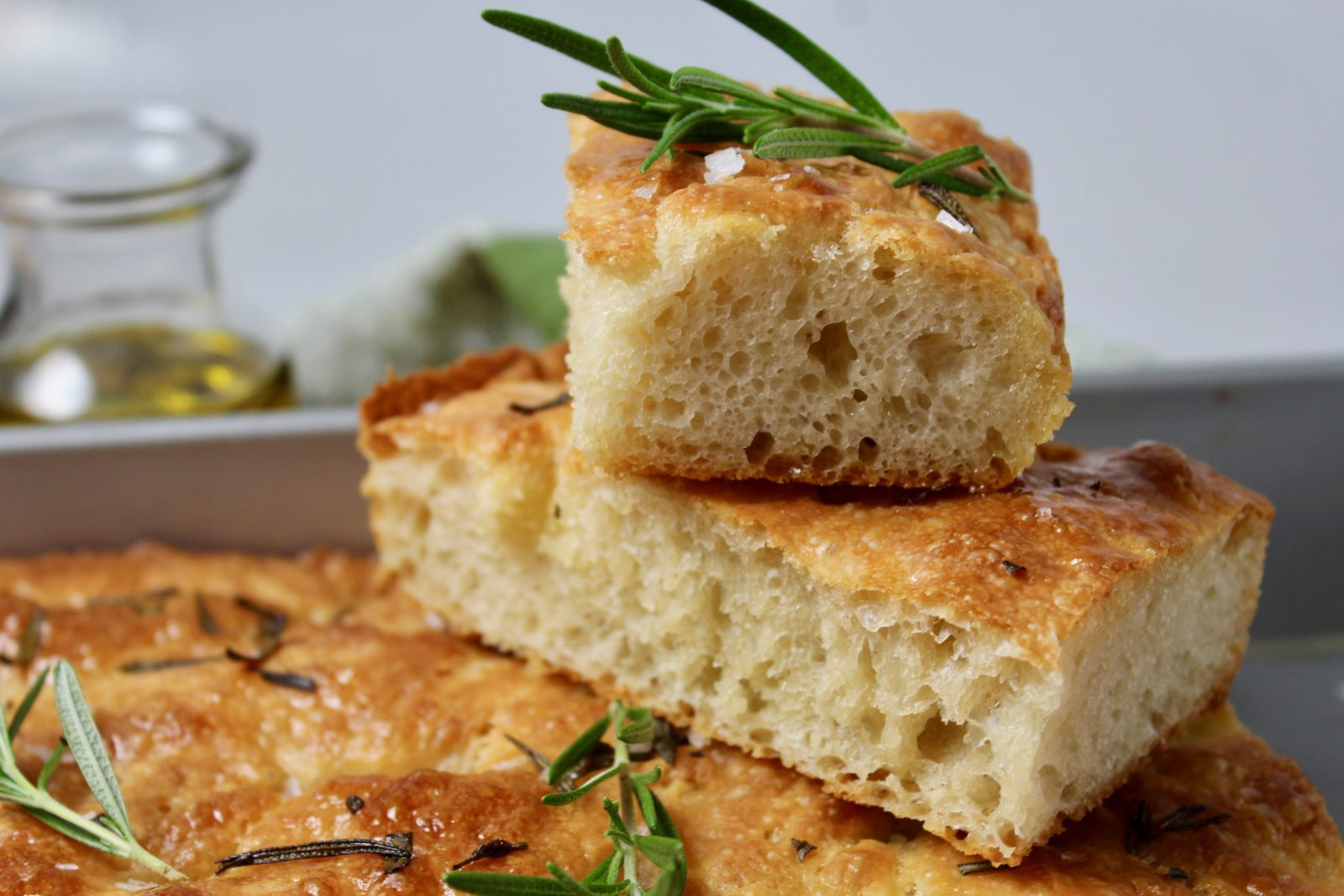 close up focaccia bread, stacked pieces, with fresh rosemary and coarse salt