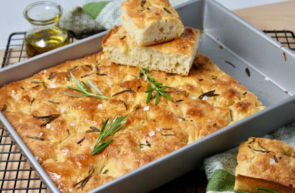 Focaccia bread in 13 x 9 x 2 metal pan topped with rosemary and coarse salt, slices cut and stacked