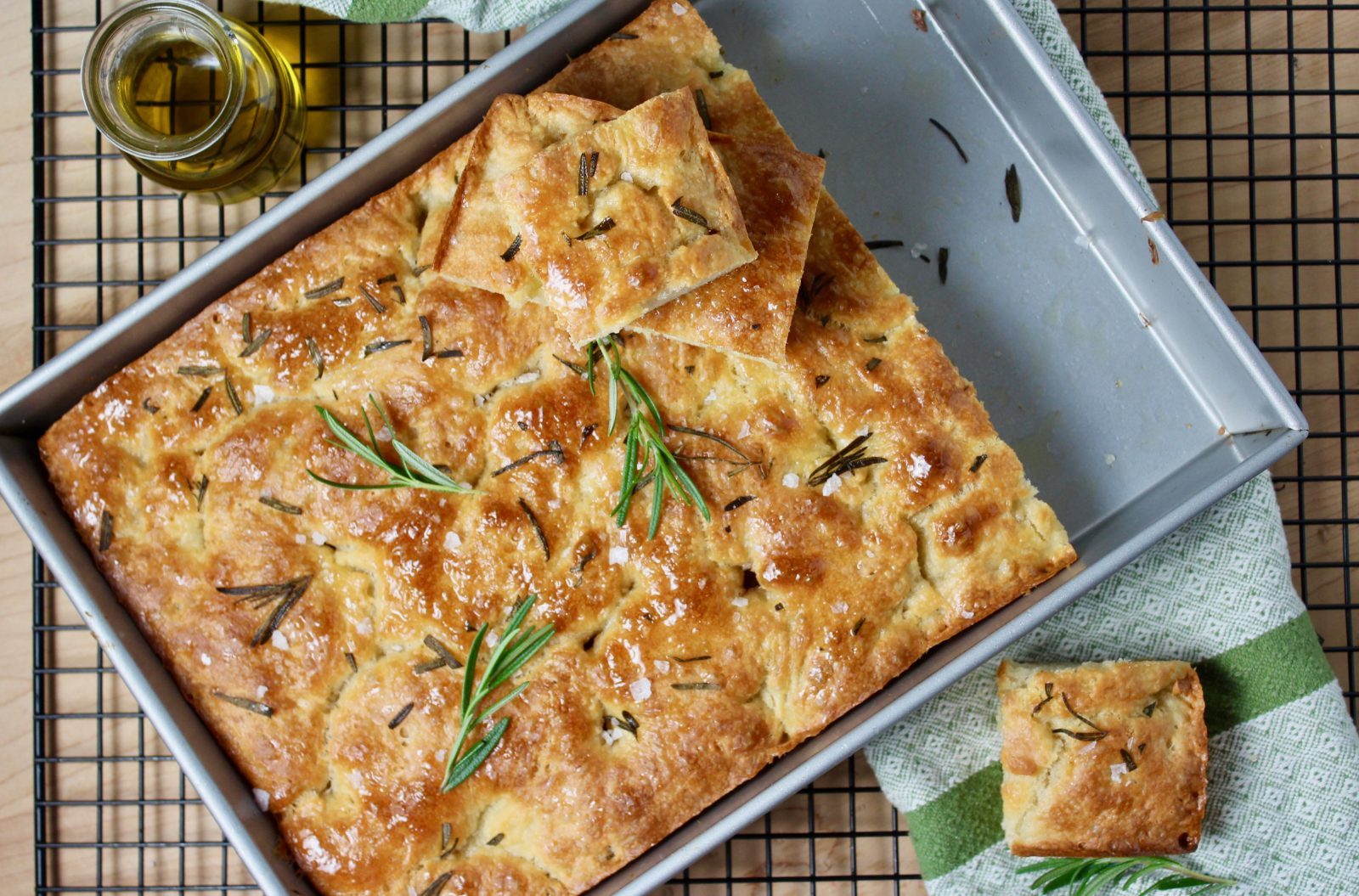 overhead photo of rosemary focaccia bread in 13 x 9 metal baking pan, topped with rosemary