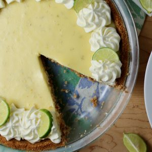 Key Lime Pie with slice cut. garnished with whipped cream rosettes and key lime slices