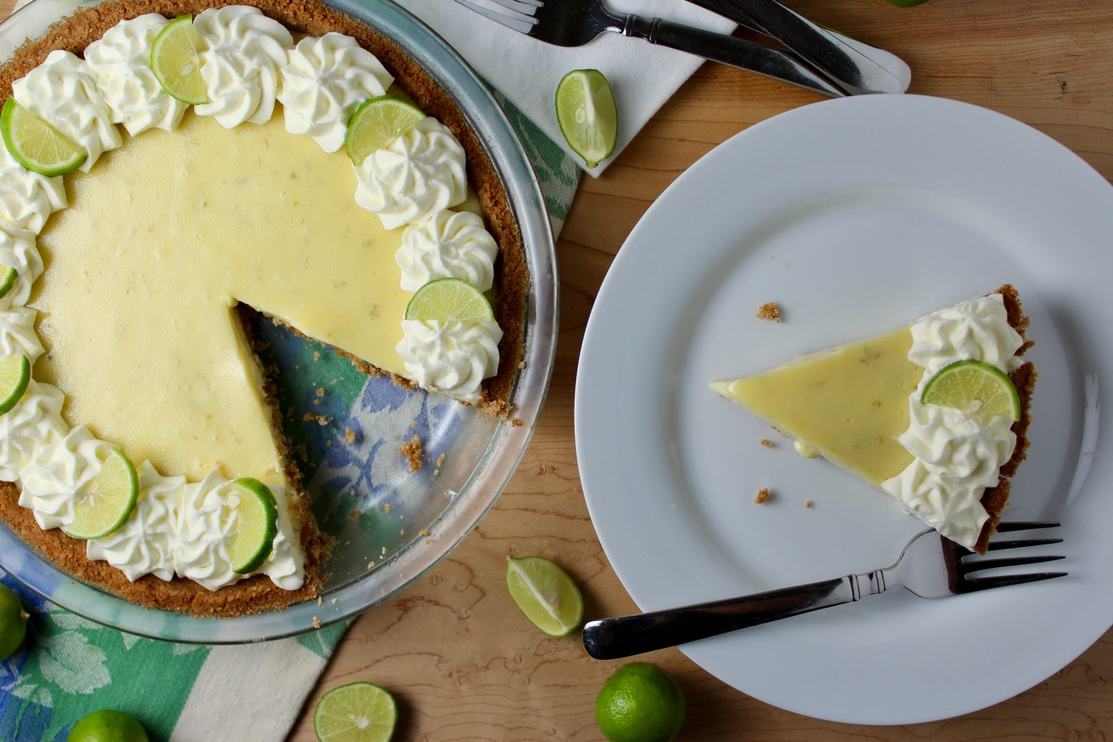 Key Lime Pie with slice on plate.  Decorated with whipped cream rosettes and key lime slices