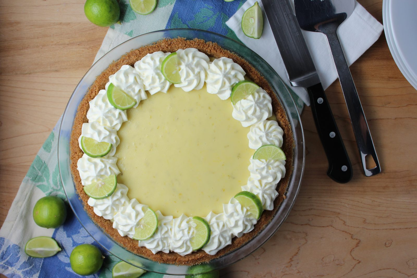 key lime pie with whipped cream rosettes and key lime slices around edge of pie