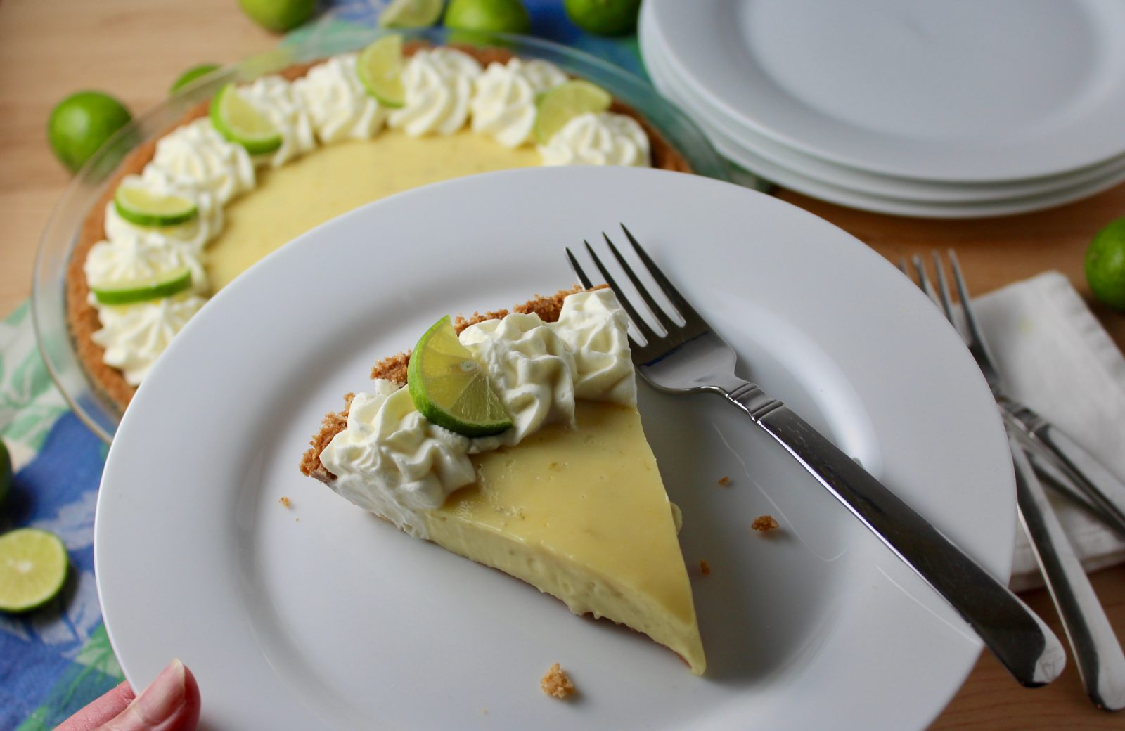 close up of slice of key lime pie on white plate.  Decorated with whipped cream rosettes and key lime slices