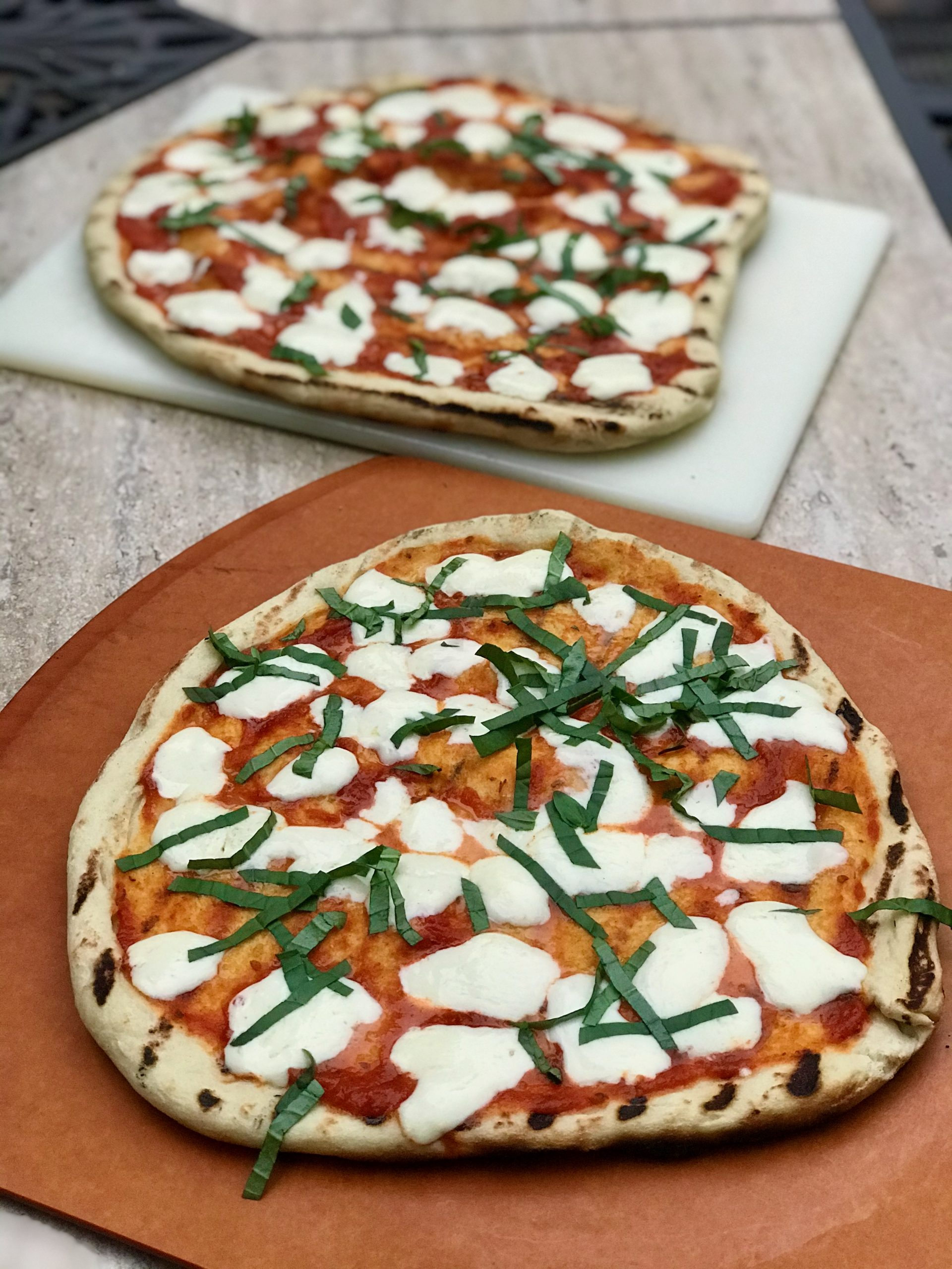 two grilled margarita pizzas on table