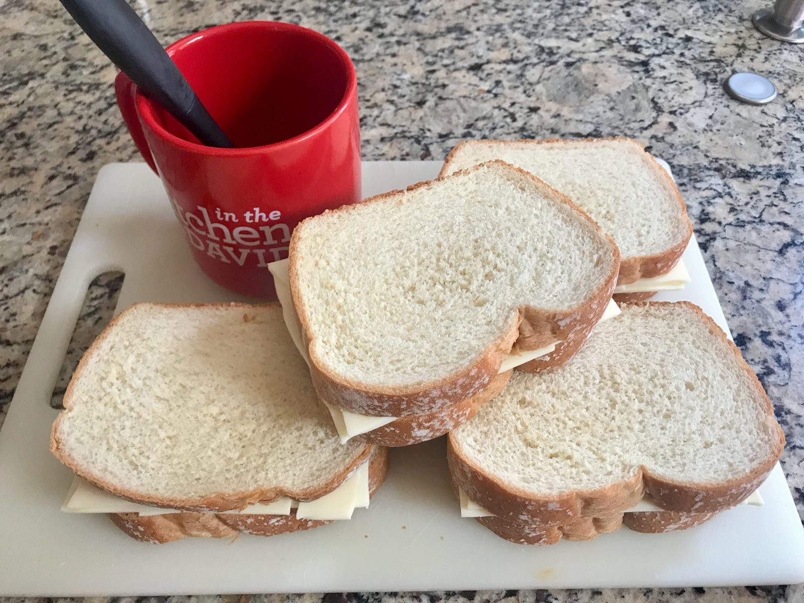 4 uncooked assembled grilled cheese sandwiches with melted butter for brushing in a red mug