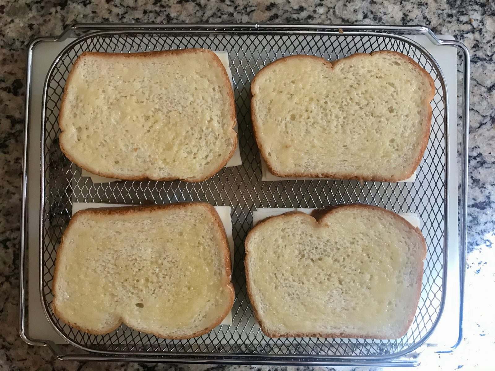 4 uncooked grilled cheese sandwiches brushed with melted butter in air fryer basket