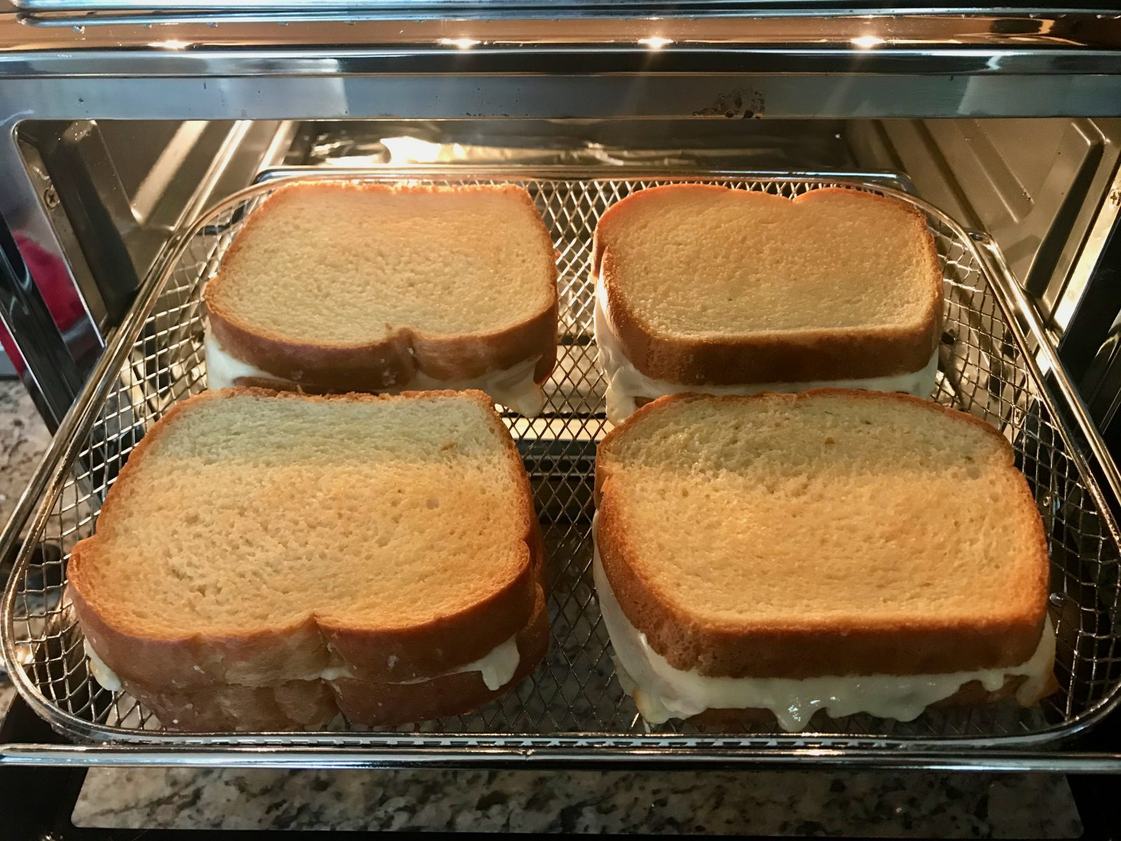 4 golden brown air fried grilled cheese sandwiches in air fryer oven - door opened and basket pulled out